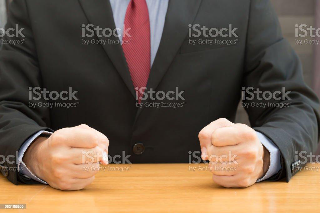 攥緊的拳頭在辦公室桌上的商人 免版稅 stock photo