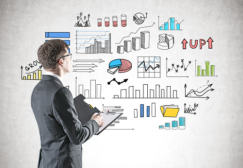 Side view of young businessman with clipboard looking at concrete wall with colorful graphs drawn on it. Concept and market analysis