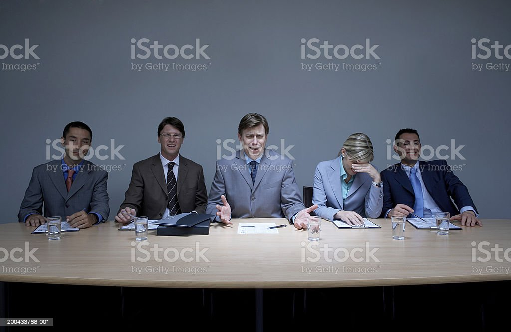 Businessman with colleagues at boardroom table, gesturing with hands stock photo