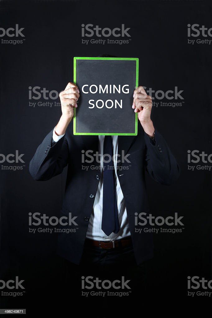 Businessman with coming soon written on slate stock photo