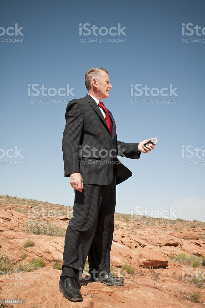 Businessman with compass in deserted place - V stock photo