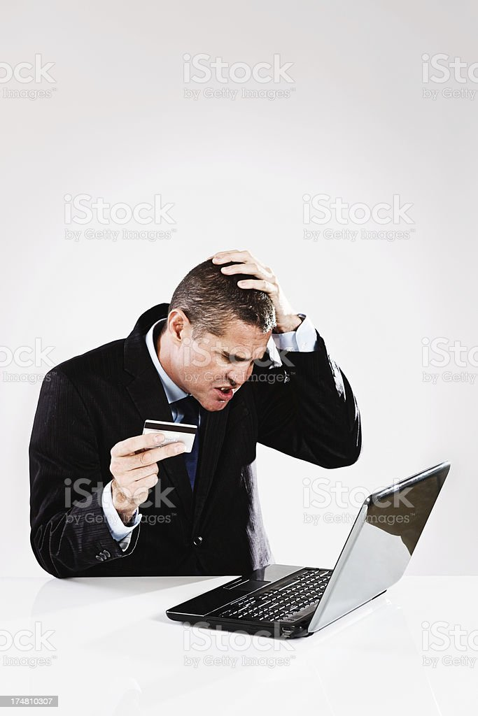 Businessman with credit card eyes laptop anxiously: e-commerce rookie? stock photo