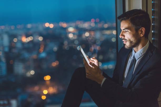 geschäftsmann mit digital-tablette spät im büro - fensterfront stock-fotos und bilder