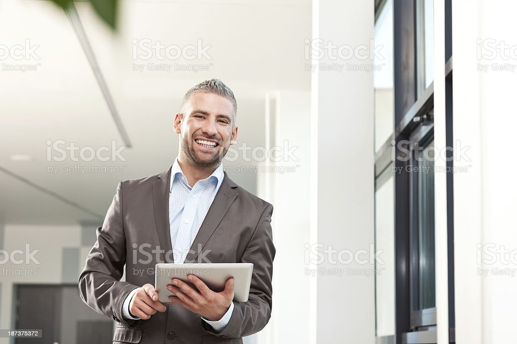 Businessman with digital tablet Portrait of cheerful businessmen holding a digital tablet and smiling at the camera. 30-34 Years Stock Photo