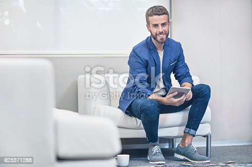 530281723istockphoto Businessman with digital tablet sitting on couch in office 625371288