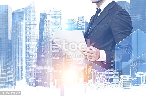 Unrecognizable bearded businessman looking at documents standing over cityscape background. Toned image double exposure