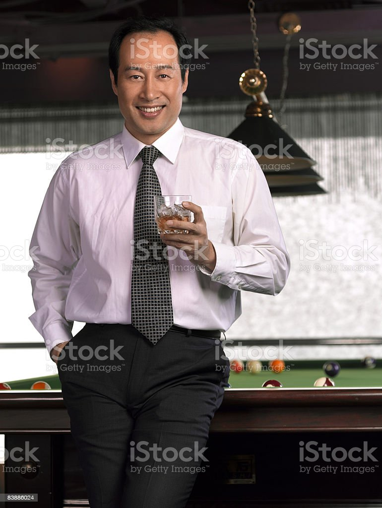 Businessman with drink leaning against pool table. royalty free stockfoto