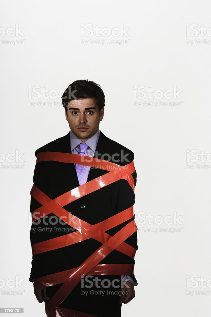 Businessman with duct tape around him stock photo