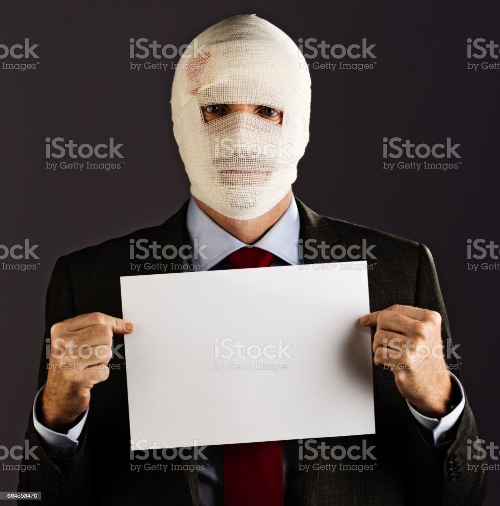 Businessman with face obscured by bandages holds blank sign stock photo