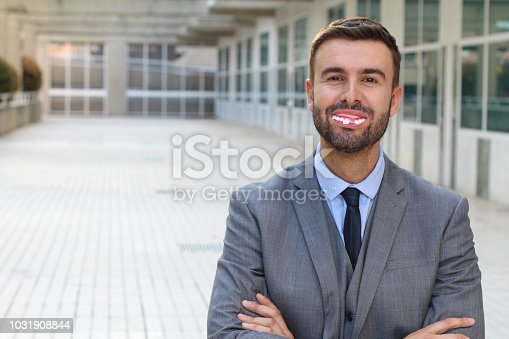 Businessman with fake dentures smiling.