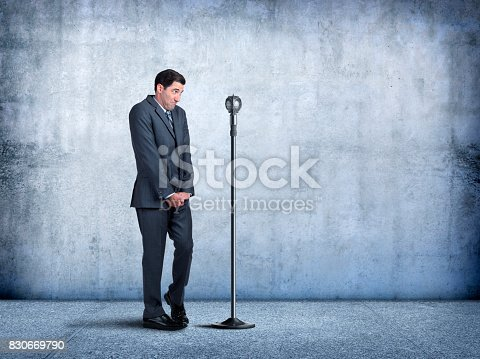 A businessman sheepishly steps up to a microphone as he is exhibits his fear of public speaking.