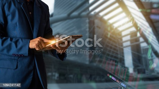 istock Businessman with finance symbols coming and city background 1094241142