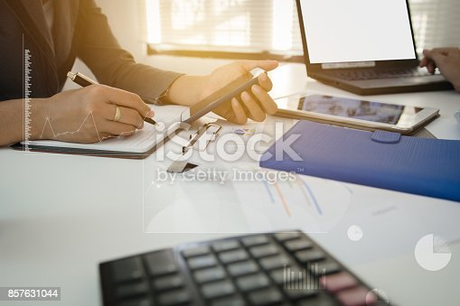 821678930 istock photo Businessman with finger touching screen of a digital phone at office on table with document graph data, Businessman calculate about cost, Finance managers task, Concept finance investment 857631044