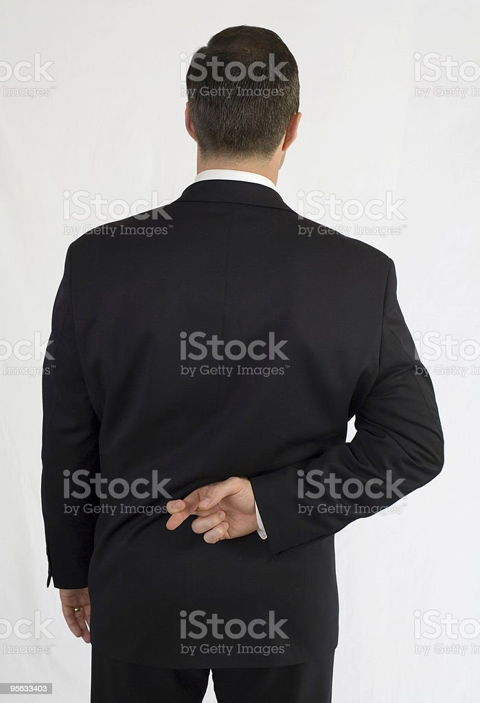 Businessman with fingers crossed behind back royalty-free stock photo