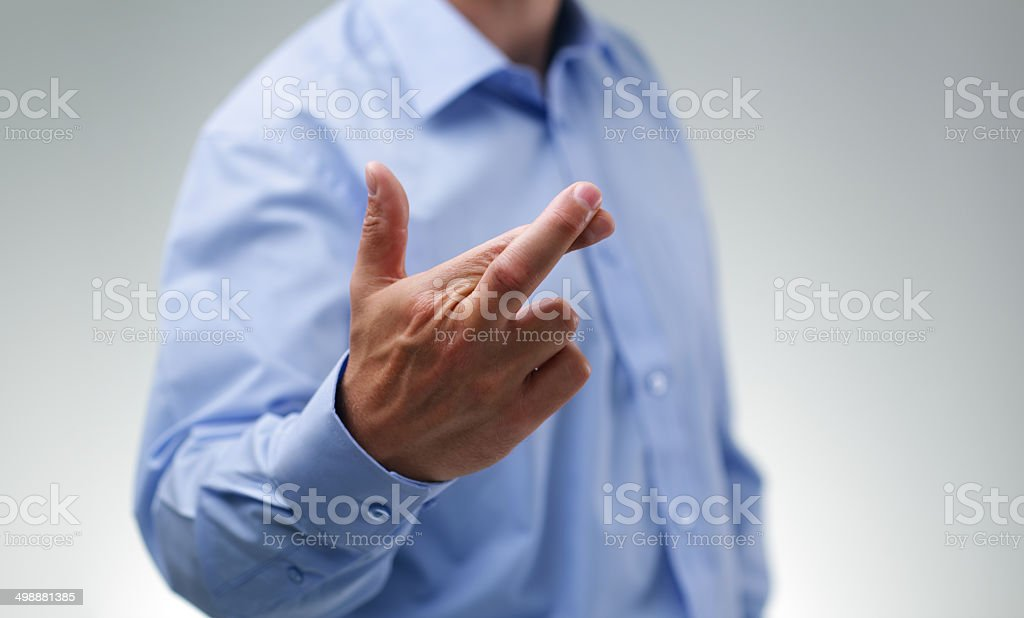 Businessman with fingers crossed stock photo