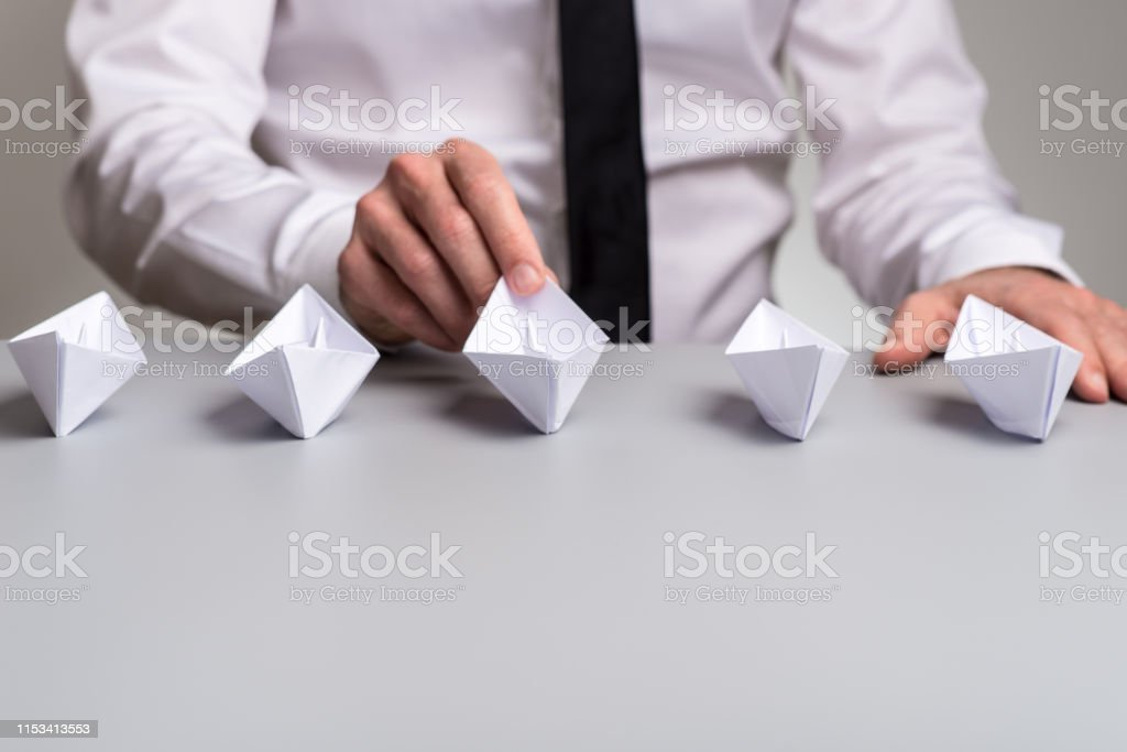 Businessman sitting at his desk with five origami paper boats in...