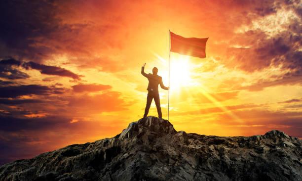 Geschäftsmann mit Flagge auf Berggipfel. Konzept für den Erfolg. – Foto