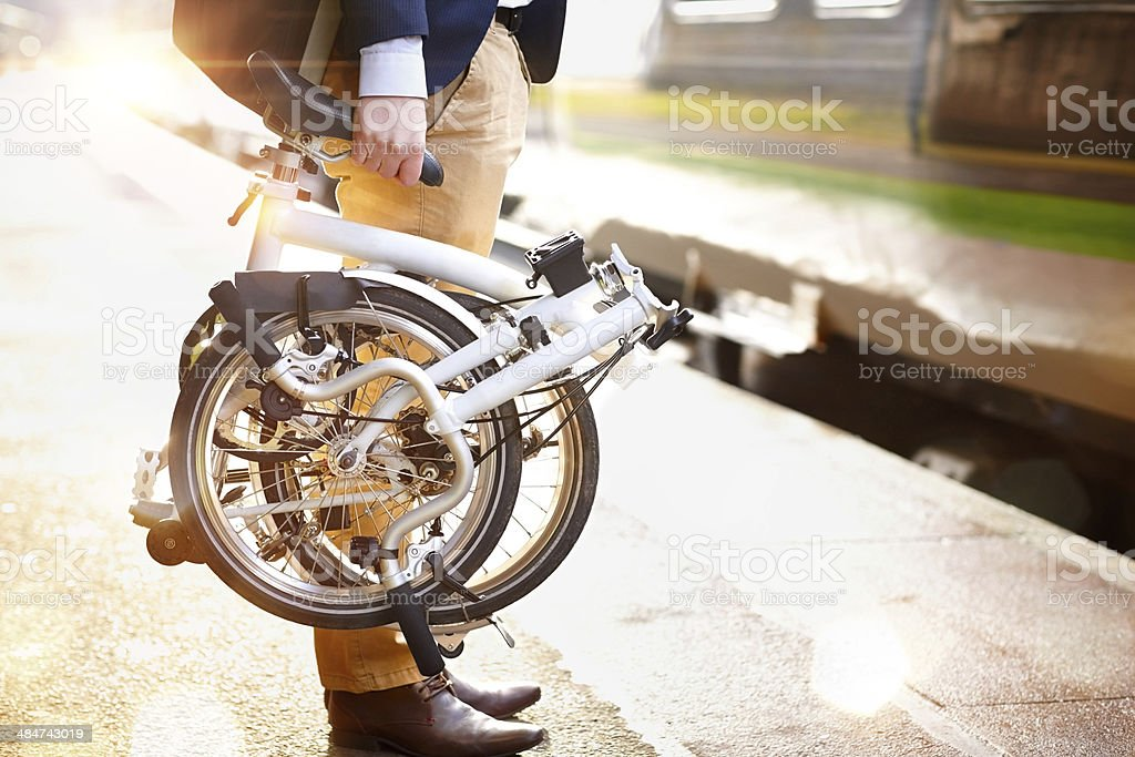 Businessman with folding bicycle at railway platform stock photo
