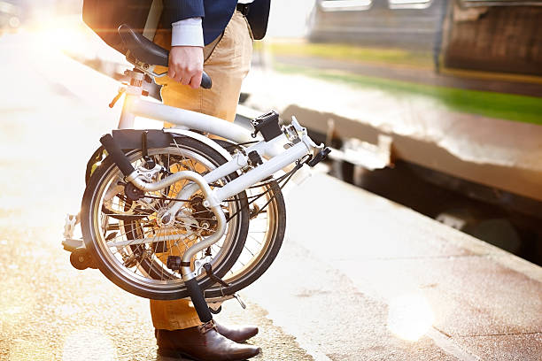 Businessman with folding bicycle at railway platform Cropped image of businessman holding his collapsible cycle waiting for his train at railway station platform foldable stock pictures, royalty-free photos & images