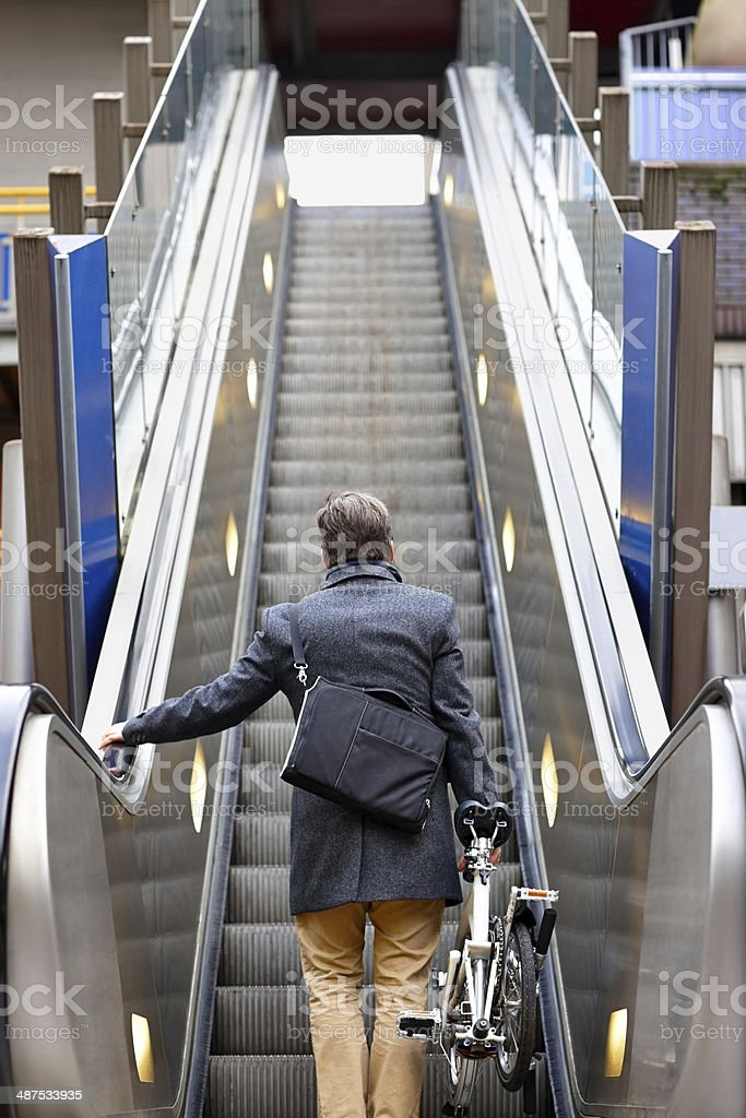 Businessman with folding bicycle on escalator stock photo