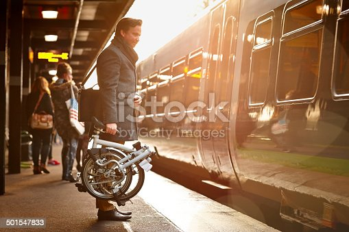 Businessman holding folding bicycle on railway platform about to board a train