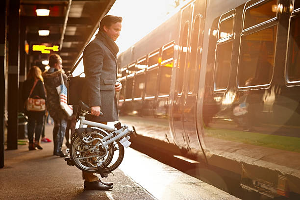 businessman with folding cycle boarding train - bisiklet stok fotoğraflar ve resimler