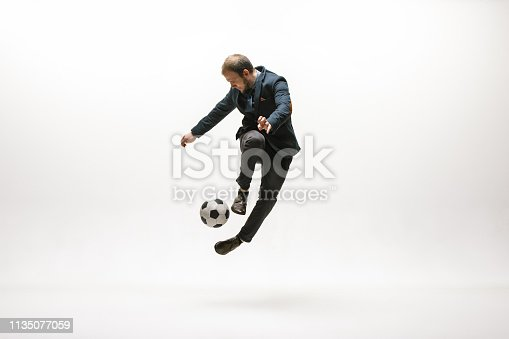 istock Businessman with football ball in office 1135077059