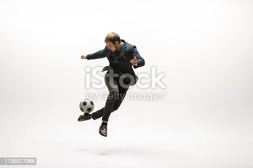 istock Businessman with football ball in office 1135077068