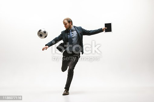 istock Businessman with football ball in office 1135077116