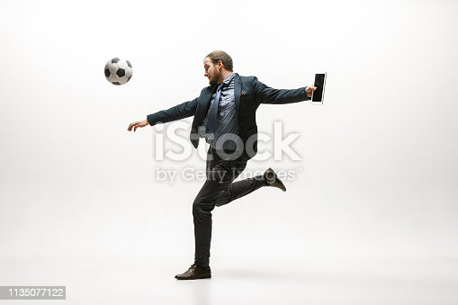 istock Businessman with football ball in office 1135077122