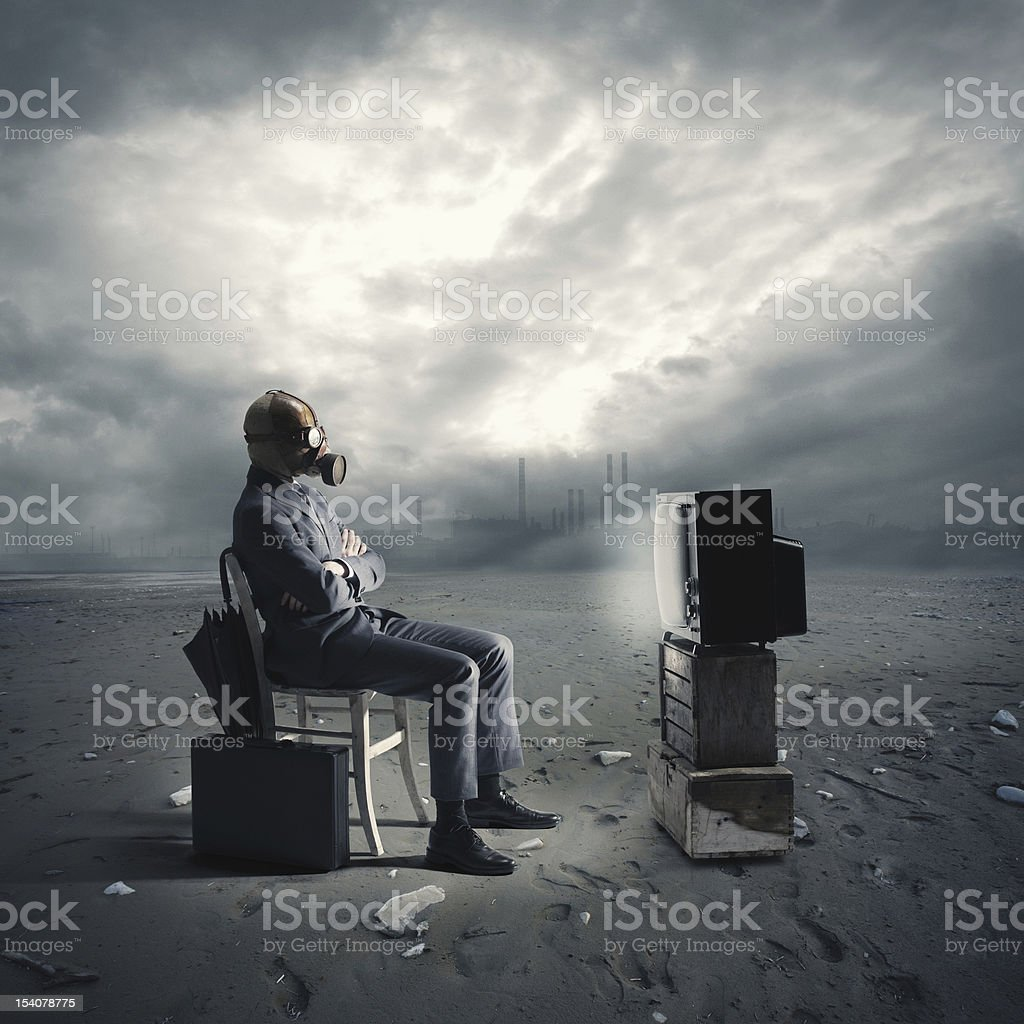 businessman with gas mask watching TV stock photo