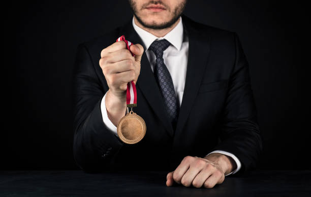 businessman with gold medal - medal stock photos and pictures