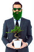 Businessman with green attitude holding bonsai.