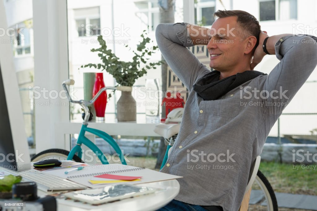 Businessman with hands behind head sitting at desk in office stock photo