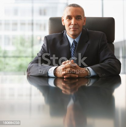 530281723istockphoto Businessman with hands clasped in front of him 150684233