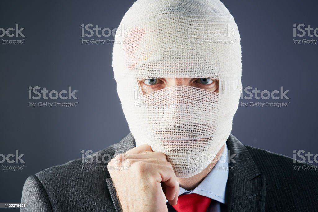 A businessman with his head covered in bandages except for his eyes...