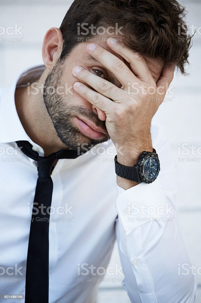 Businessman with head in hands, looking at camera Lizenzfreies stock-foto