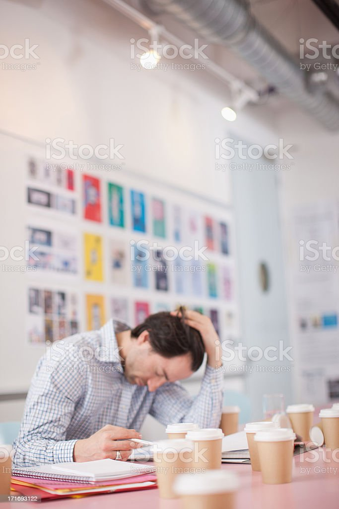 Businessman with head in hands surrounded by coffee cups in office