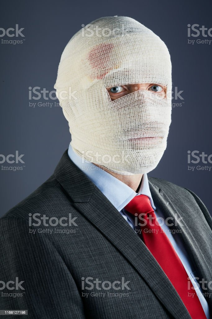 A formally dressed businessman has his had completely obscured by...