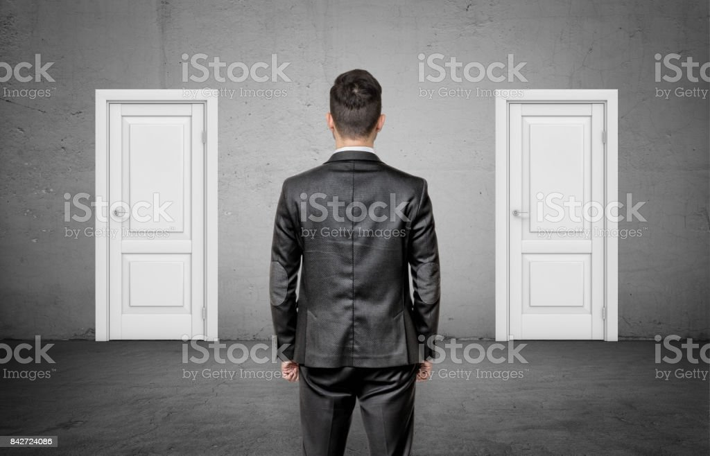 A businessman with his back turned stands between two identical closed white doors royalty-free stock photo