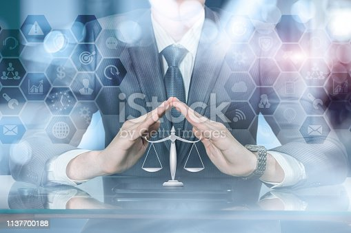 488389267istockphoto A businessman with his hands in protective position under scale of justice on a tablet. 1137700188