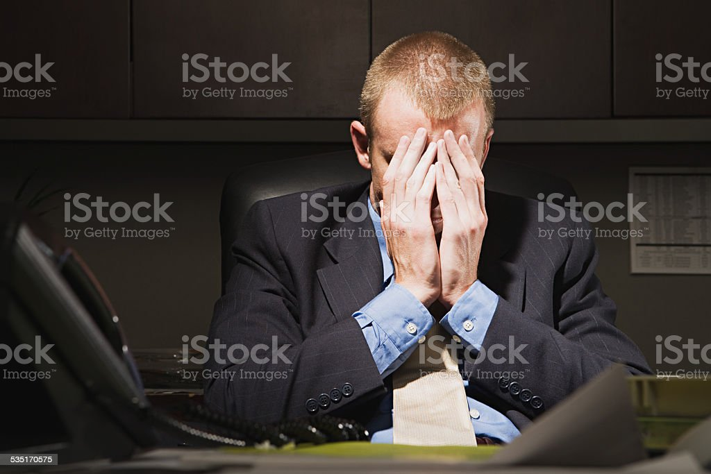Businessman with his head in his hands stock photo