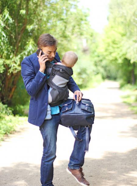 geschäftsmann mit seinem sohn in einer schlinge gespräche auf dem smartphone - kleinkind busy bags stock-fotos und bilder