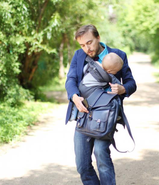 geschäftsmann mit seinem sohn in einer schlinge versuchen, öffnet sich ein rucksack-w - kleinkind busy bags stock-fotos und bilder
