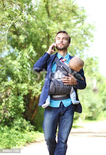 istock businessman with his son in a sling walks and talks on the smart 906341582