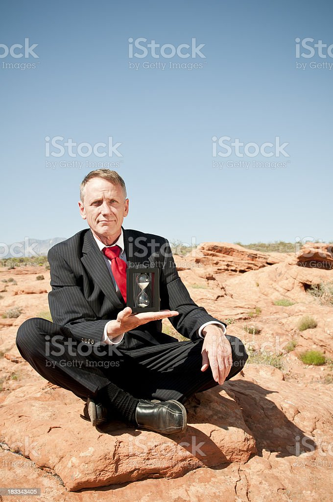 Businessman with hourglass in deserted place - II stock photo