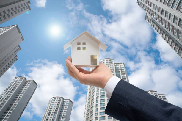 Businessman with house model on hand. Real estate concept stock photo