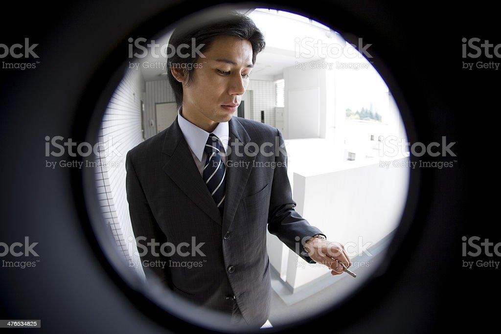 Businessman with key seen through peep window stock photo