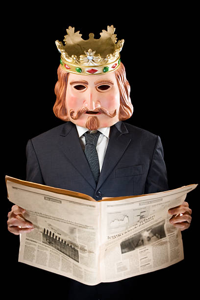Businessman with king mask reading news stock photo
