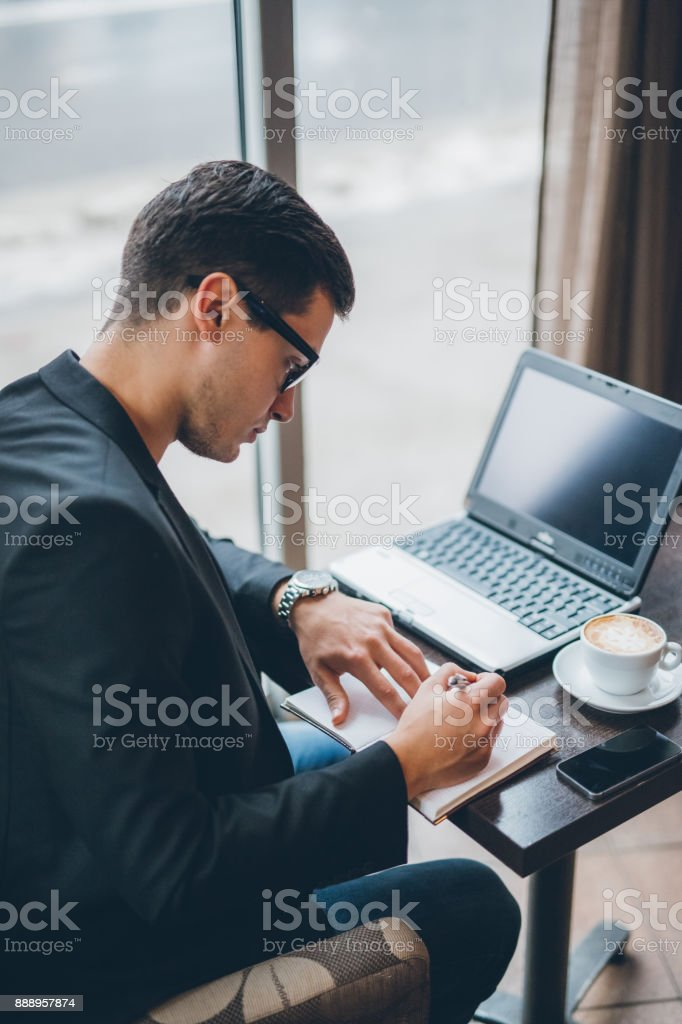 Businessman with laptop and coffee on table stock photo